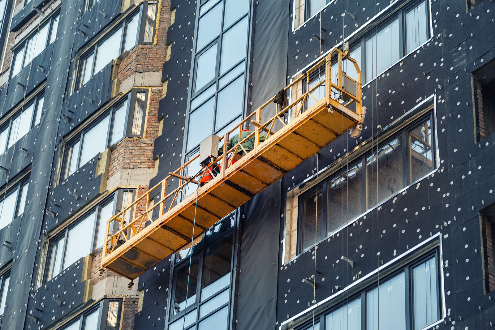 workers outside on elevated swing stage scaffolding platform