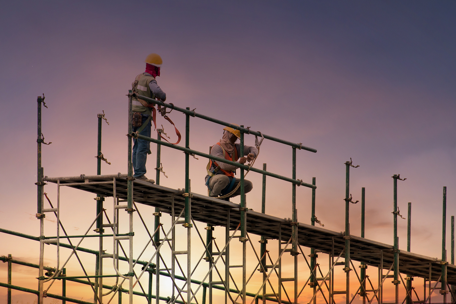 construction workers at height on scaffolding with sunset in background
